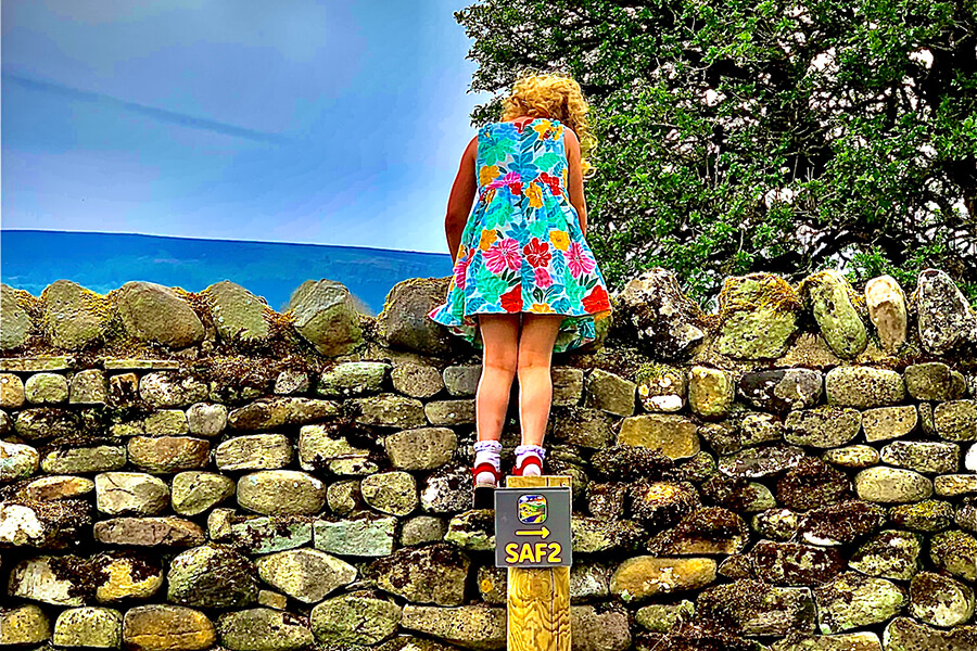 Masons Campsite Girl Loking ove rteh wall at Bolton Abbey North Yorkshire